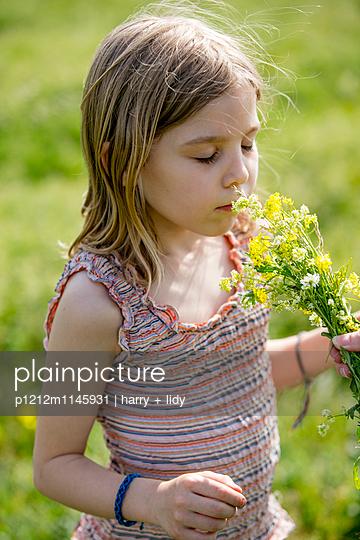Mädchen in der Wiese riecht an einem Blumenstrauß - p1212m1145931 von harry + lidy