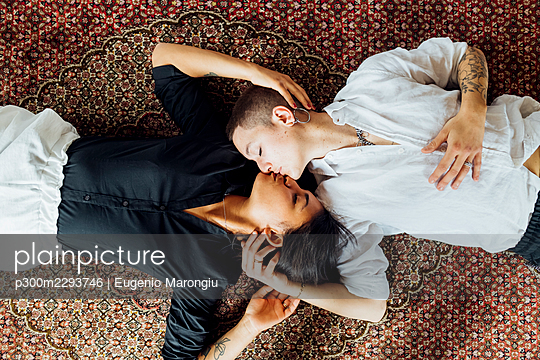 Young multi-ethnic lesbians kissing while lying on carpet at home - p300m2293746 by Eugenio Marongiu