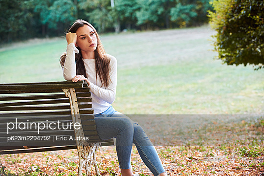 Thoughtful young woman sitting on bench in park - p623m2294792 by Eric Audras