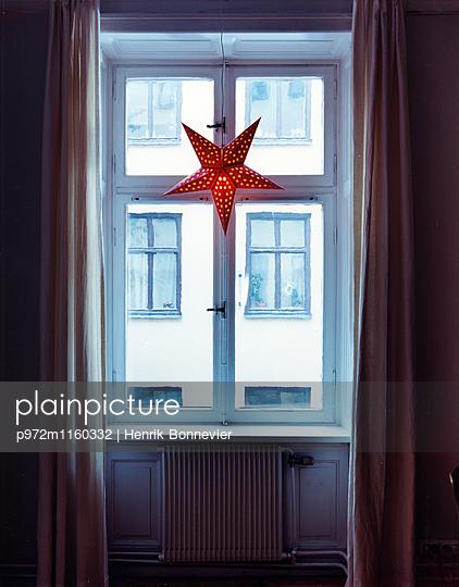 Beleuchteter Weihnachtsstern am Fenster - p972m1160332 von Henrik Bonnevier