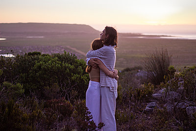 Teenage couple embracing at twilight - p1640m2245873 by Holly & John