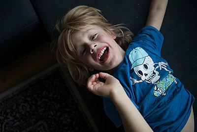 Portrait of exuberant boy lying on couch - p300m2058952 von Johanna Lohr