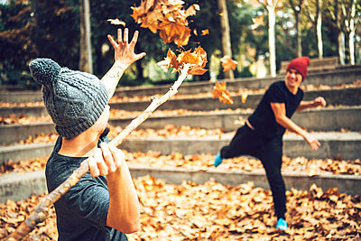 Young male friends playing with autumn leaves in public park - p300m2206683 by klublu
