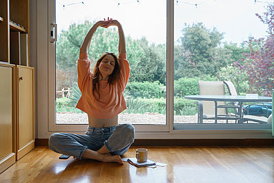 Beautiful woman stretching while sitting cross-legged by sliding door at home - p300m2281357 by VITTA GALLERY