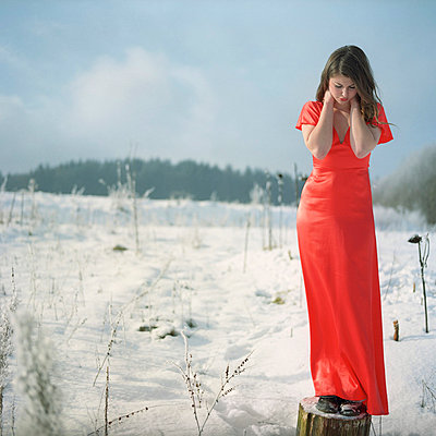 Woman in a red dress in winter - p7870189 by Forster-Martin