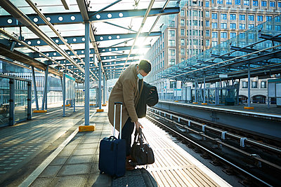 UK, London, Man waiting at train station platform - p924m2271269 by Peter Muller