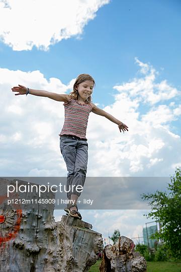 Mädchen springt vom Baumstumpf - p1212m1145909 von harry + lidy