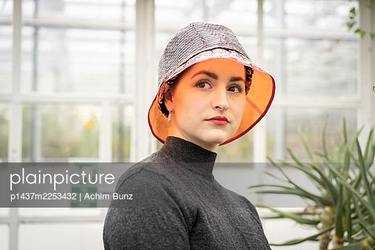 Junge Frau mit Fischerhut in einem Tropenhaus - p1437m2253432 von Achim Bunz