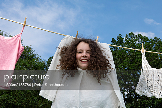 Portrait of young woman with brown ringlets in white dress drying on clothesline - p300m2155784 von Petra Stockhausen