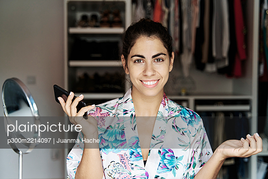 Smiling young woman holding smart phone while sitting at home - p300m2214097 by Juanma Hache