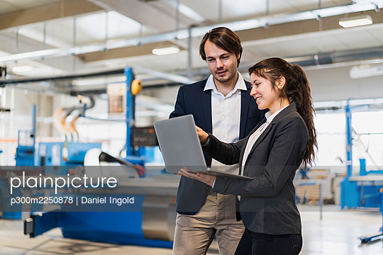 Business people working on laptop while standing at industry - p300m2250878 by Daniel Ingold