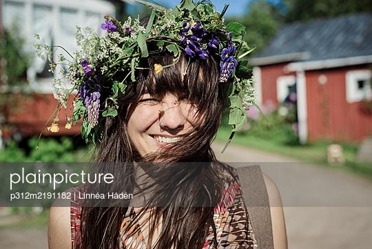 Happy woman wearing flower wreath - p312m2191182 by Linnéa Hådén
