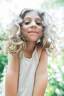 Low angle portrait of happy girl at park - p1166m1486042 by Cavan Images