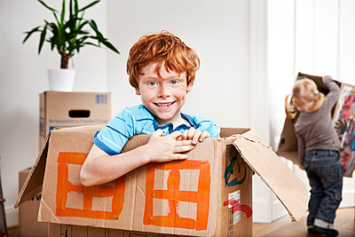 Happy boy looking out of a cardboard box in new apartment with sister in background - p300m1525837 by Mareen Fischinger