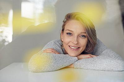 Portrait of smiling blond woman leaning on table - p300m2012931 von Philipp Nemenz