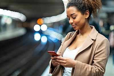 Smiling young woman using cell phone at subway station platform - p300m2167646 by William Perugini