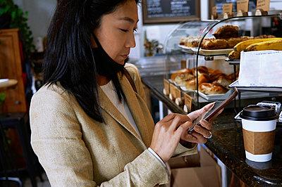 Female customer using smart phone to pay at bakery - p300m2273693 by Arman Zhenikeyev