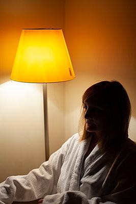 Portrait einer sitzenden traurigen Frau im Schatten einer Lampe - p795m2087453 von JanJasperKlein