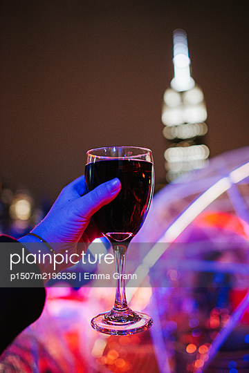 drinking  Redwine at night, Empire State Building in the background - p1507m2196536 by Emma Grann