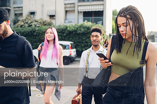 Group of friends using smartphones in the city - p300m2202869 by Eugenio Marongiu