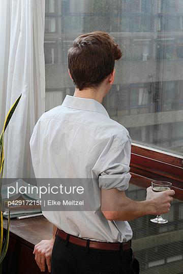 Businessman with wine looking out window - p42917215f by Elke Meitzel