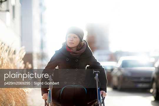 Woman in wheelchair in street - p429m2069295 by Sigrid Gombert