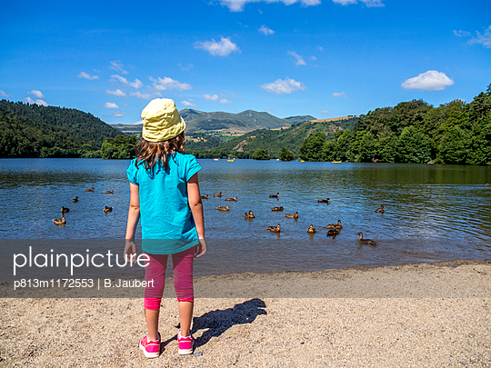 Little girl near a lake watching the ducks. France. - p813m1172553 by B.Jaubert