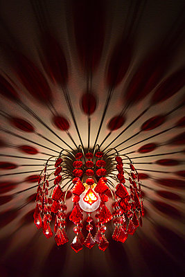 Looking up to a chandelier style lamp shade hanging from a  ceiligng inside a house, the red plastic jewels casting long patterned shadows across the white painted roof. - p1057m1510620 by Stephen Shepherd