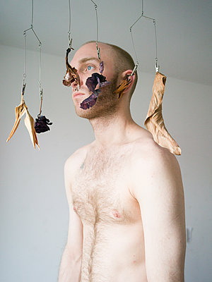 Bare-chested man behind hanging mobile - p1267m2043238 by Wolf Meier