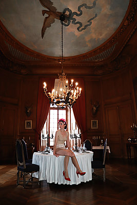 Woman in vintage lingerie on a table in a castle - p1521m2214962 by Charlotte Zobel