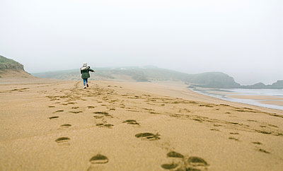 Girl running on the beach on a foggy winter day - p300m1228582 by David Pereiras