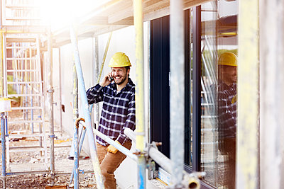 Happy worker on the phone a construction site - p300m2198718 by MiJo