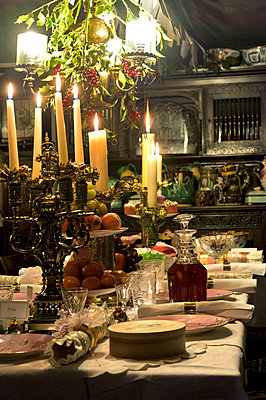 Lit candles on dining room table set for Christmas dinner in Cheltenham country home - p349m790925 by Polly Eltes