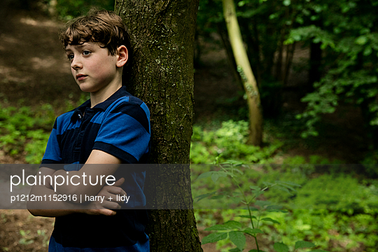 Junge lehnt an einem Baum im Wald - p1212m1152916 von harry + lidy