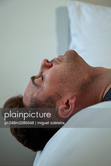 Head of man hanging over edge of bed - p1248m2289348 by miguel sobreira