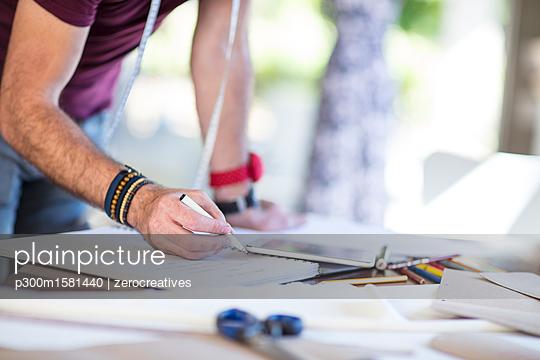 Close-up of fashion designer taking notes on table - p300m1581440 von zerocreatives