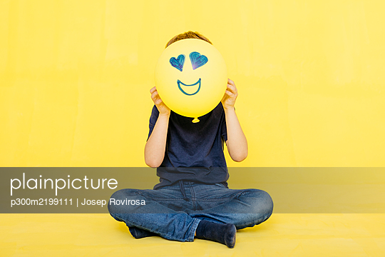 Boy holding yellow balloon with anthropomorphic face against colored background - p300m2199111 by Josep Rovirosa