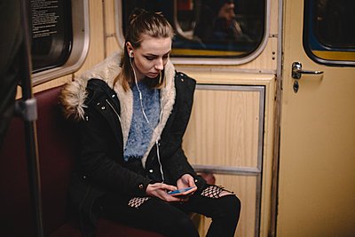 Young woman using smart phone while traveling in subway train - p1166m2138115 by Cavan Images