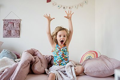 young girl stretching and yawning in the morning in her bed at home - p1166m2147389 by Cavan Images