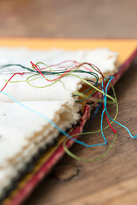 Old needle case with sewing needles and strands of colourful thread. - p1433m1589003 by Wolf Kettler