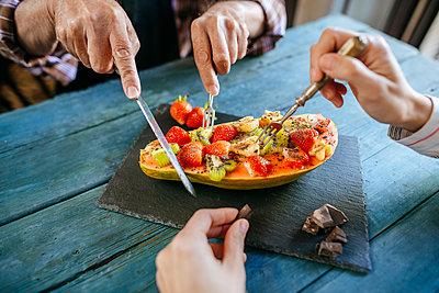Close-up of hands of man and woman eating papaya with kiwi, banana and strawberries - p300m1535742 by Kiko Jimenez