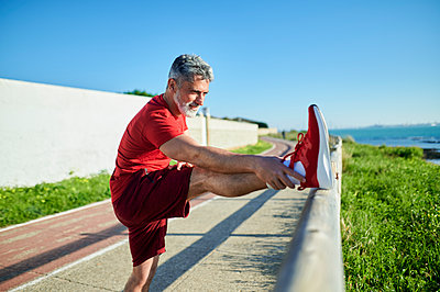 Smiling man stretching leg on railing during sunny day - p300m2275601 by Kiko Jimenez