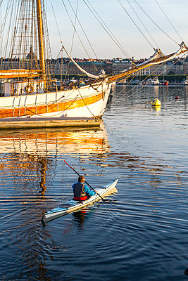 Man kayaking on sea - p312m1103605f by Henrik Trygg