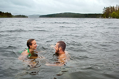 Couple treading water and talking in Kezar Lake - p343m1167900 by Monica Donovan