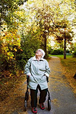 Senior woman sitting on a walking frame in park - p352m2119836 by Lena Katarina Johansson