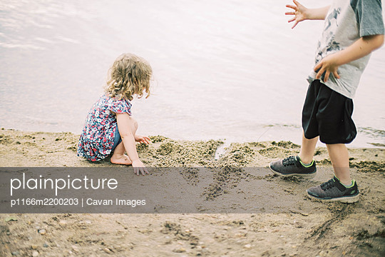Two children playing in the sand by the shore of a lake - p1166m2200203 by Cavan Images