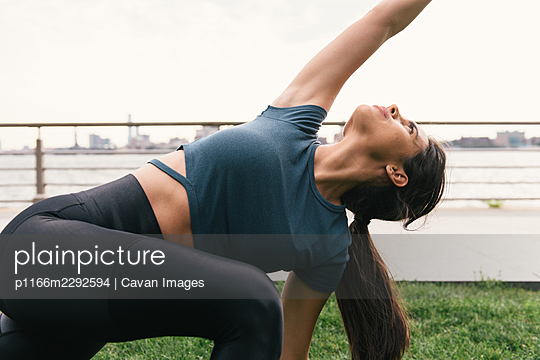 Close side profile image of woman stretching on grass - p1166m2292594 by Cavan Images