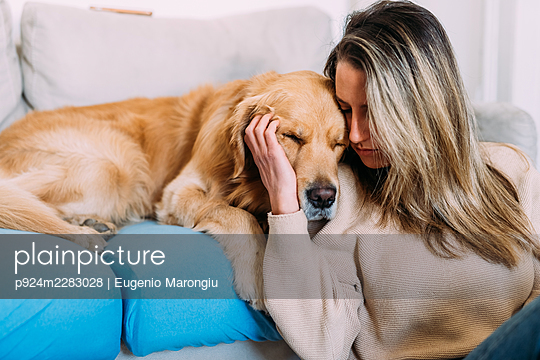 Italy, Young woman with dog at home - p924m2283028 by Eugenio Marongiu