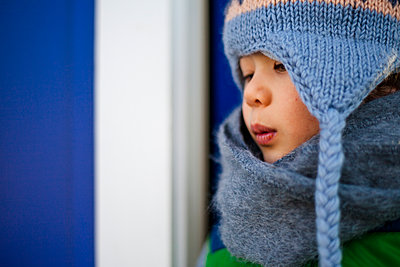 Close-up of thoughtful boy in warm clothing looking away while standing at doorway - p1166m2009259 by Cavan Images
