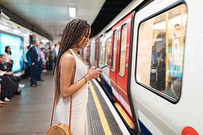 Young woman waiting at subway station platform looking at cell phone, London, UK - p300m2132595 von William Perugini